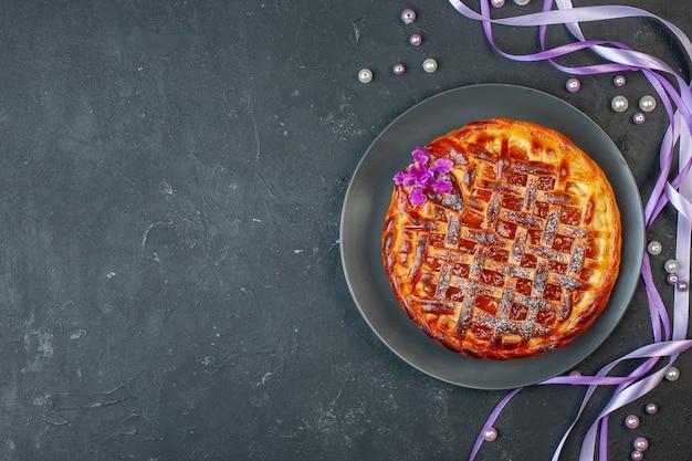 Bovenaanzicht heerlijke fruitige taart met jam binnen plaat op donkere tafel