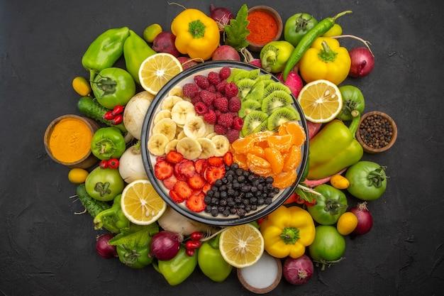 Bovenaanzicht heerlijke fruitsalade binnen bord met vers fruit op een donkere tropische fruitboom exotische rijpe dieet foto