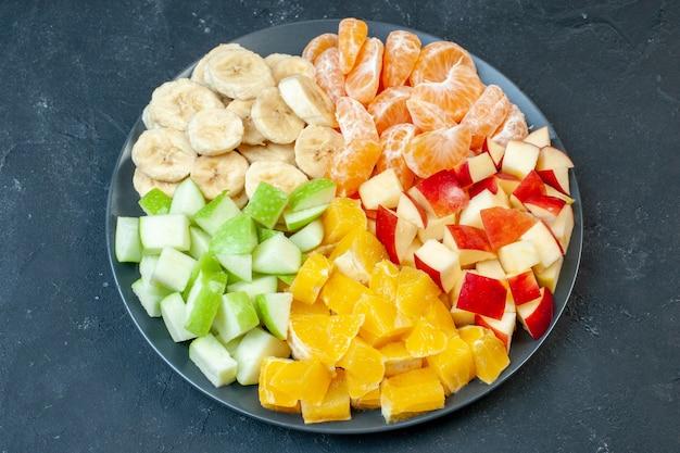 Bovenaanzicht heerlijke fruitsalade gesneden mandarijnen appels, bananen en sinaasappels op donkere achtergrond