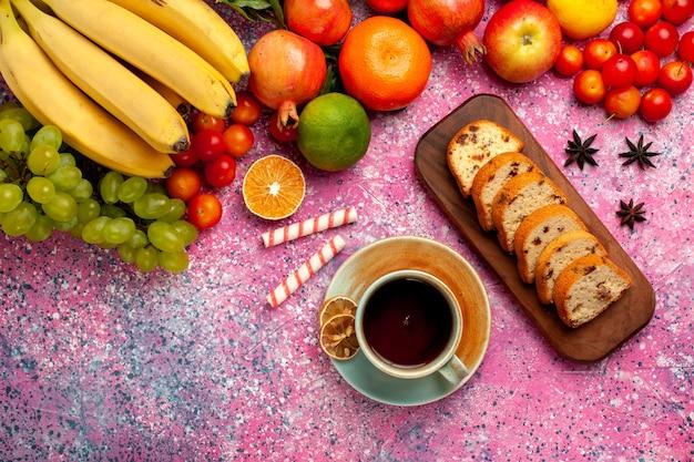 Bovenaanzicht heerlijke fruitsamenstelling met gesneden taarten en kopje thee op roze oppervlak