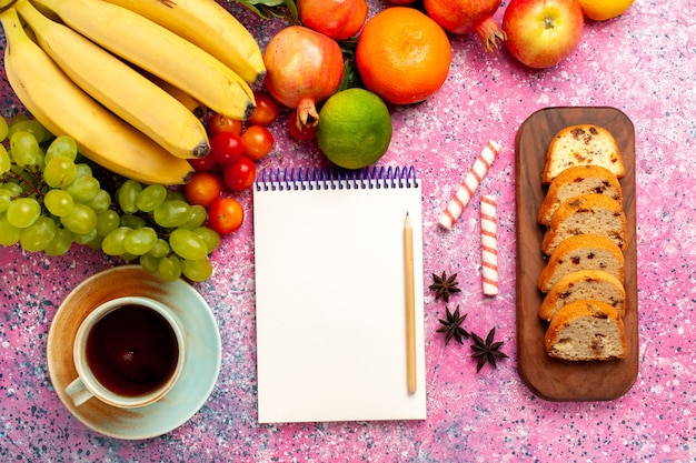 Bovenaanzicht heerlijke fruitsamenstelling met gesneden taarten en thee op het roze bureau