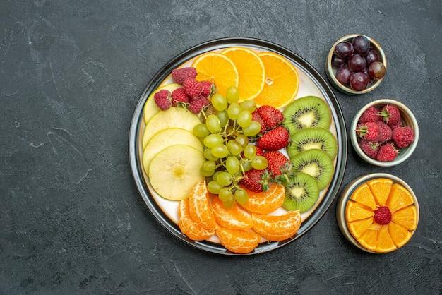 Bovenaanzicht heerlijke fruitsamenstelling vers en gesneden fruit op de donkere achtergrond rijp vers gezondheidsdieet fruit zacht