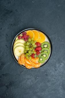 Bovenaanzicht heerlijke fruitsamenstelling vers gesneden en zacht fruit op de donkere achtergrond rijp vers zacht gezondheidsdieet