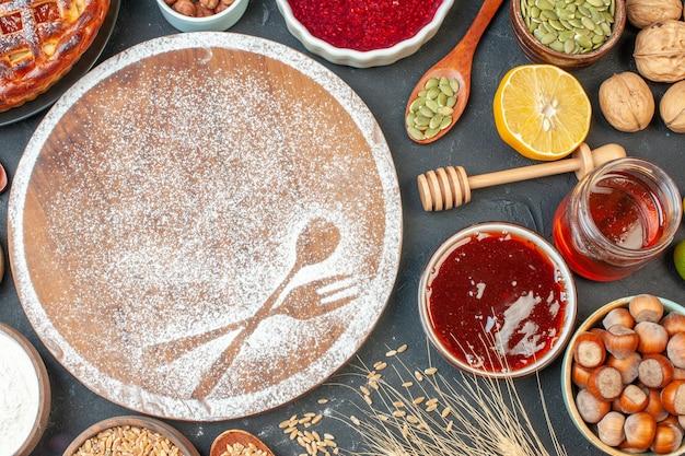 Bovenaanzicht heerlijke fruittaart met noten, honing en jam op donkere tafel