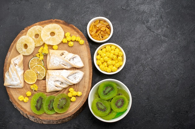 Bovenaanzicht heerlijke gebakjes met gedroogde ananasringen en kiwi's op grijs bureau