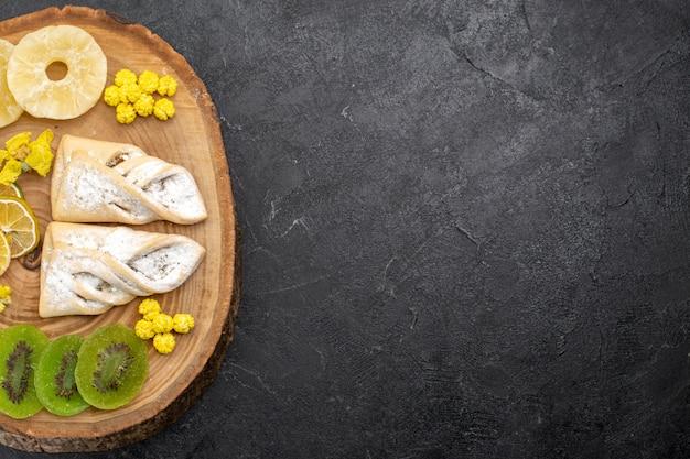 Bovenaanzicht heerlijke gebakjes met plakjes gedroogd fruit op de grijze ruimte
