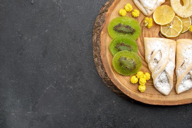 Bovenaanzicht heerlijke gebakjes met plakjes gedroogd fruit op grijze vloer fruit droge rozijnen zoete cake