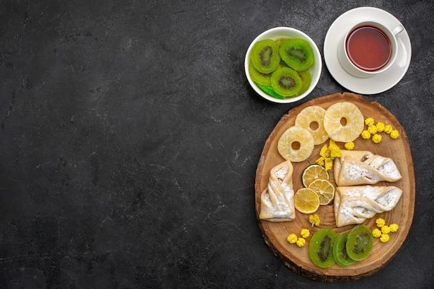 Bovenaanzicht heerlijke gebakjes met thee gedroogde ananasringen en kiwi's op donkergrijze ruimte
