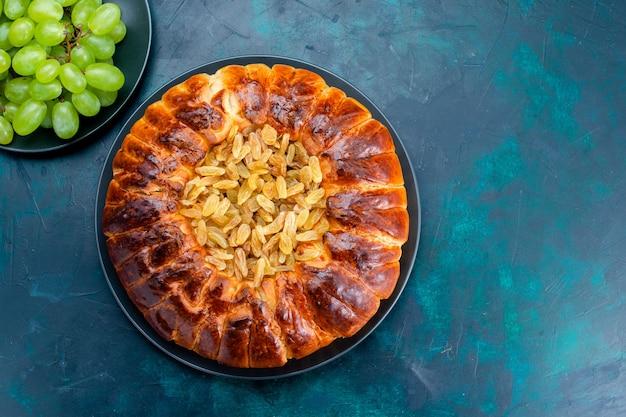 Bovenaanzicht heerlijke gebakken cake met rozijnen en verse groene druiven op donkerblauw bureau taart taart suiker zoet koekdeeg