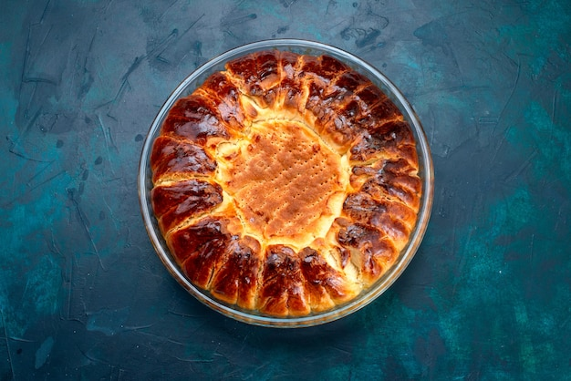 Bovenaanzicht heerlijke gebakken cake ronde gevormde zoete binnen glazen pan op de lichtblauwe achtergrond.