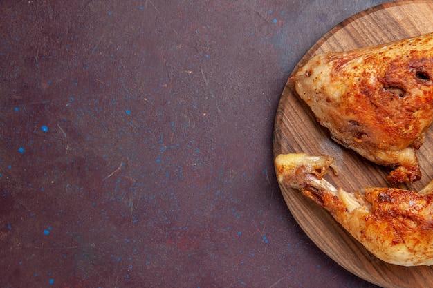 Bovenaanzicht heerlijke gebakken kip gekookt vlees plakjes op donker bureau