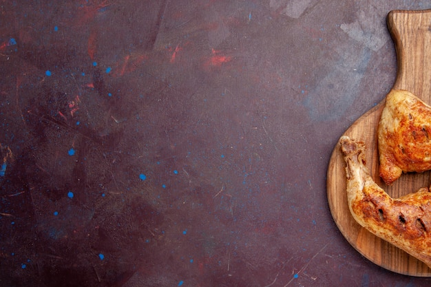 Bovenaanzicht heerlijke gebakken kip gekookt vlees plakjes op donkere ruimte