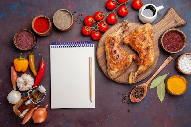 Bovenaanzicht heerlijke gebakken kip met kruiden en groenten op de donkere ruimte