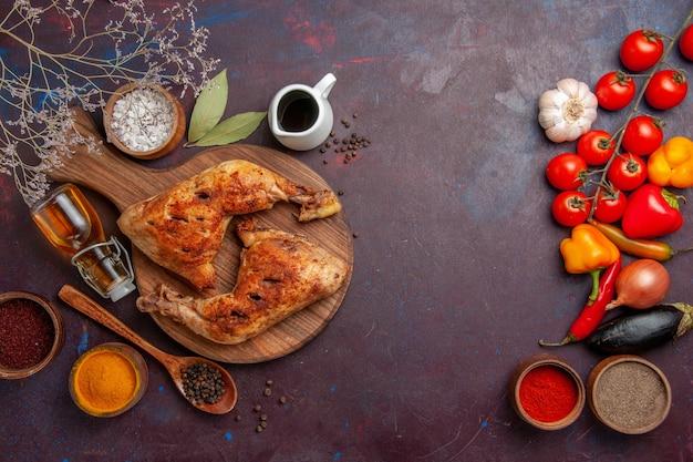 Bovenaanzicht heerlijke gebakken kip met kruiden op de donkere ruimte