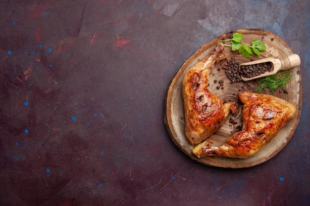 Bovenaanzicht heerlijke gebakken kip met peper op donker bureau