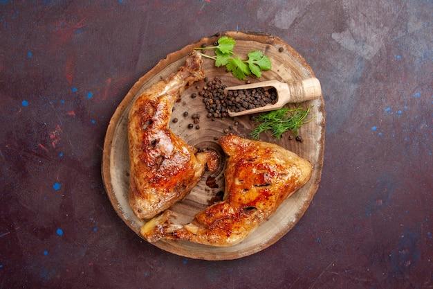 Bovenaanzicht heerlijke gebakken kip met peper op donkere ruimte