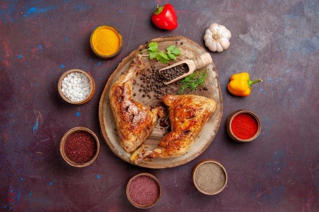 Bovenaanzicht heerlijke gebakken kip met verschillende kruiden op de donkere ruimte
