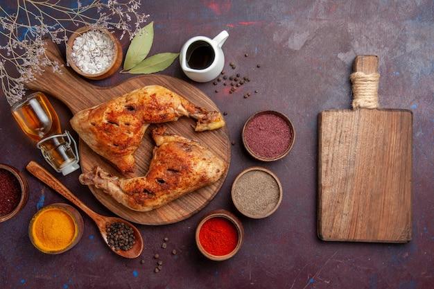 Bovenaanzicht heerlijke gebakken kip met verschillende kruiden op donker bureau