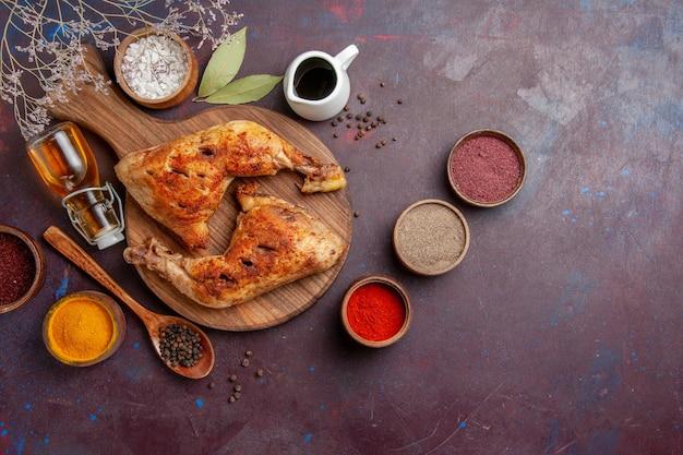 Bovenaanzicht heerlijke gebakken kip met verschillende kruiden op donkerpaarse ruimte