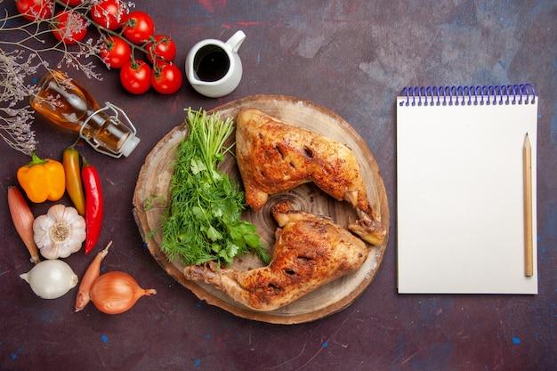 Bovenaanzicht heerlijke gebakken kip met verse groenten en greens op donkere ruimte