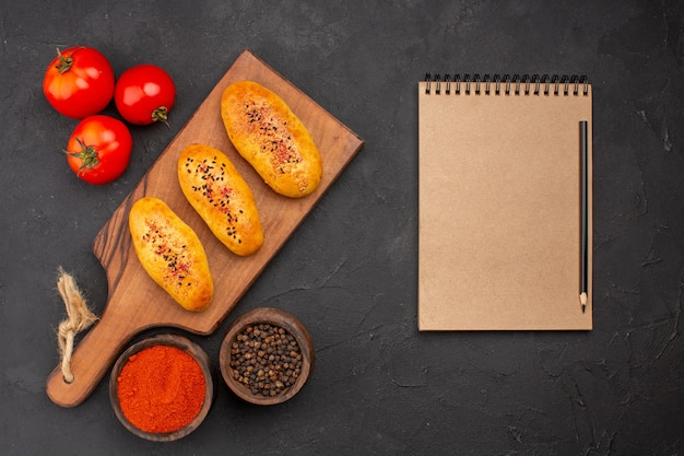 Bovenaanzicht heerlijke gebakken pasteitjes vers uit de oven met tomaten op de grijze achtergrond taart oven gebak deeg vlees cake bakken