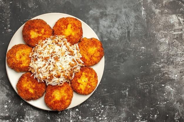 Bovenaanzicht heerlijke gebakken schnitzels met gekookte rijst op de donkere vleesgerecht fotomaaltijd
