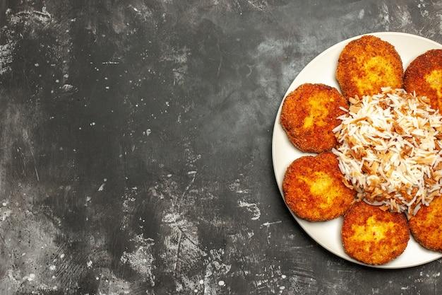 Bovenaanzicht heerlijke gebakken schnitzels met gekookte rijst op donker bureau vleesgerecht fotomaaltijd
