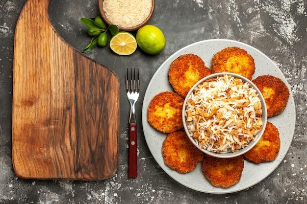 Bovenaanzicht heerlijke gebakken schnitzels met gekookte rijst op donkere oppervlak rissole vleesgerecht