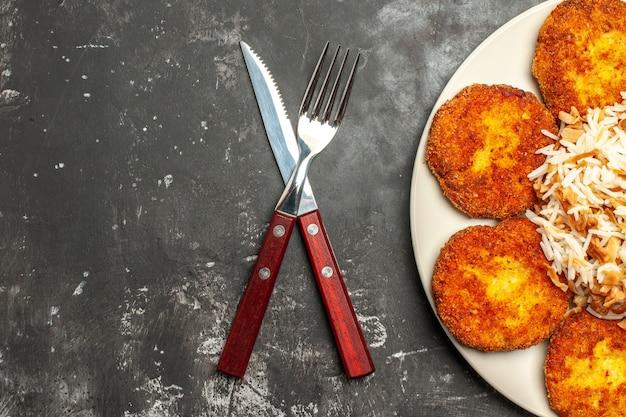 Bovenaanzicht heerlijke gebakken schnitzels met gekookte rijst op donkere oppervlak vleesfoto maaltijd