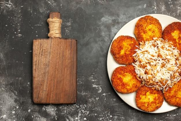 Bovenaanzicht heerlijke gebakken schnitzels met gekookte rijst op donkere oppervlak vleesgerecht foto