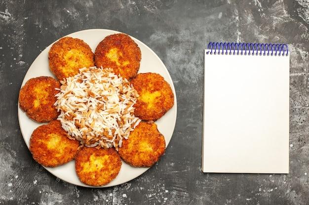 Bovenaanzicht heerlijke gebakken schnitzels met gekookte rijst op donkere vloer vleesgerecht fotomaaltijd