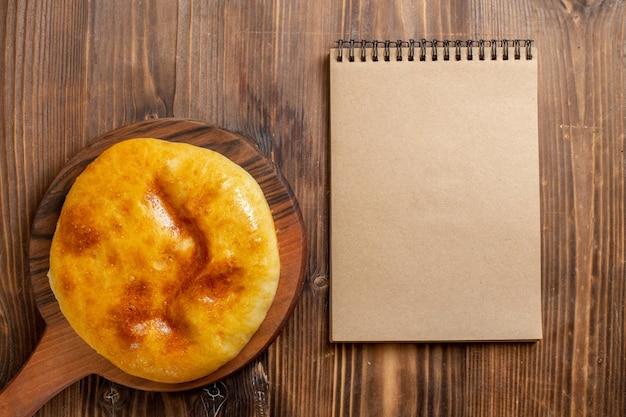Bovenaanzicht heerlijke gebakken taart met aardappelpuree binnen op de bruine houten bureau cake hotcake taart bak deeg maaltijd