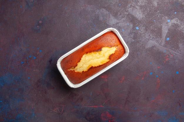 Bovenaanzicht heerlijke gebakken taart zoete cake voor thee op donkere bureau cake biscuit zoete taart suiker deeg thee