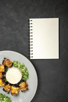 Bovenaanzicht heerlijke gekookte aubergines met rijst en notitieblok op donkere oppervlakte diner eten koken rijstmaaltijd