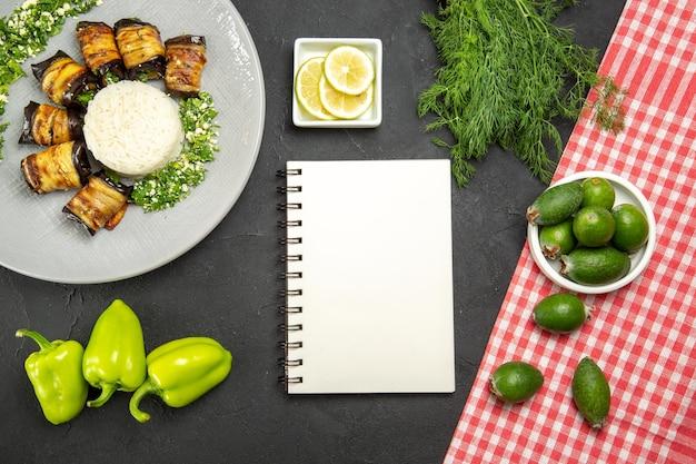 Bovenaanzicht heerlijke gekookte aubergines met rijst feijoa en schijfjes citroen op donkere ondergrond diner eten koken rijstmeel