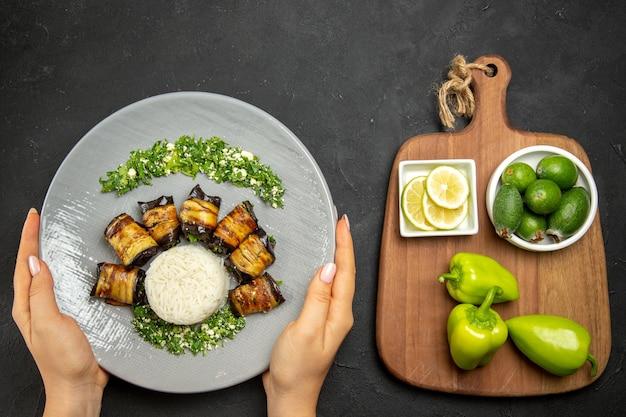 Bovenaanzicht heerlijke gekookte aubergines met schijfjes rijst, citroen en feijoa op donkere ondergrond diner eten bakolie rijstmeel