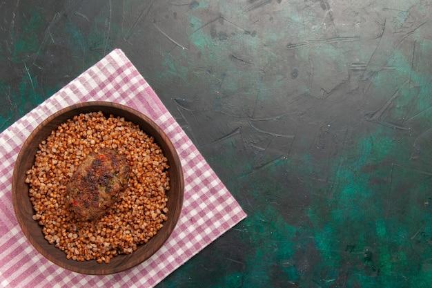 Bovenaanzicht heerlijke gekookte boekweit met kotelet op donkergroen oppervlak ingrediënt maaltijd groenteschotel