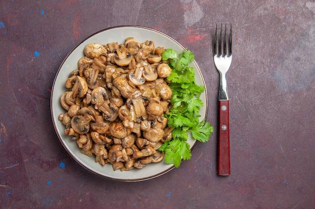 Bovenaanzicht heerlijke gekookte champignons met groen op de donkere achtergrond schotel diner maaltijd voedsel plant wild