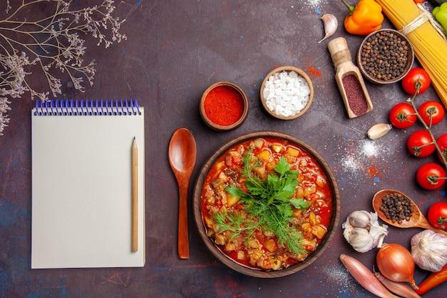 Bovenaanzicht heerlijke gekookte groenten gesneden met greens en kruiden op de donkere achtergrond soep maaltijdsaus