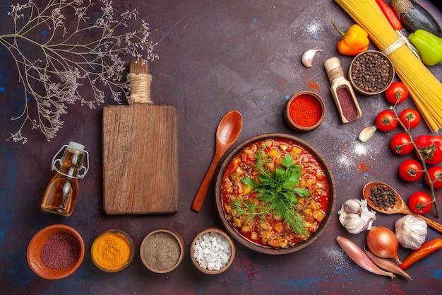 Bovenaanzicht heerlijke gekookte groenten gesneden met verschillende kruiden op de donkere achtergrond soep eten saus maaltijd groente