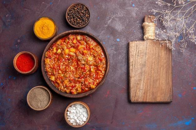 Bovenaanzicht heerlijke gekookte groenten met verschillende kruiden op de donkere achtergrond soep saus maaltijd plantaardig voedsel
