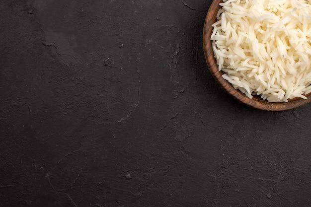 Bovenaanzicht heerlijke gekookte rijst gewoon smakelijke rijst in bruine plaat op de donkere ruimte