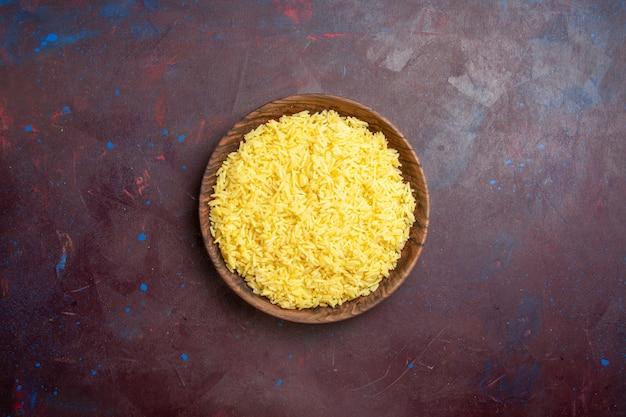 Bovenaanzicht heerlijke gekookte rijst in bruine plaat op donker bureau