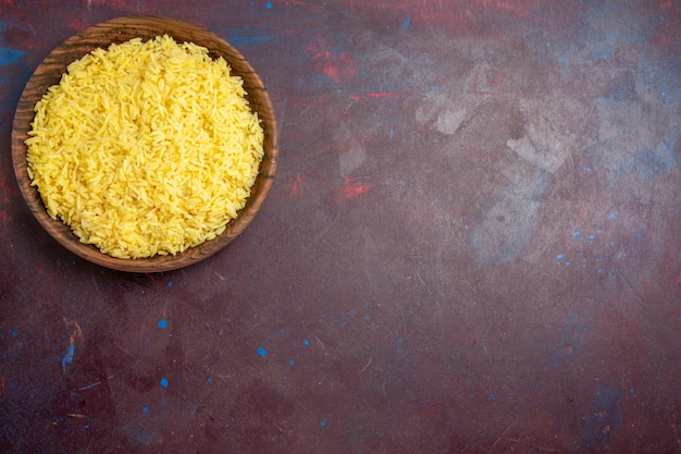 Bovenaanzicht heerlijke gekookte rijst in bruine plaat op het donkere bureau