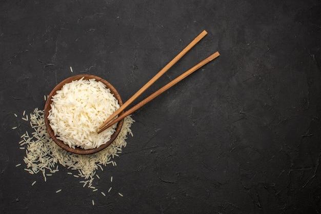 Bovenaanzicht heerlijke gekookte rijst smakelijke oosterse maaltijd op donkere ruimte