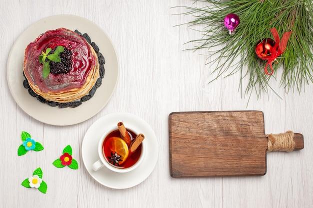 Bovenaanzicht heerlijke gelei pannenkoeken met rozijnen fruitige gelei en kopje thee op wit bureau jam cake gelei biscuit dessert zoet