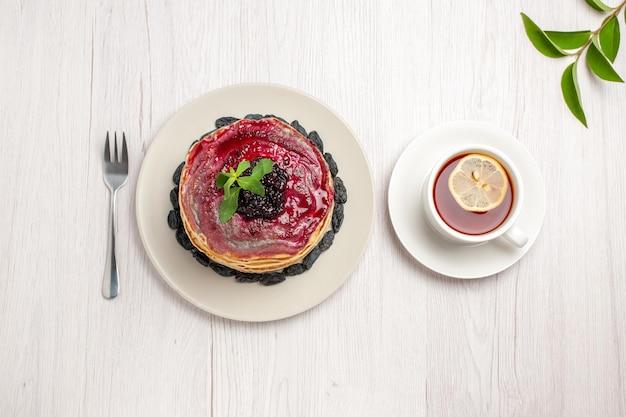 Bovenaanzicht heerlijke gelei pannenkoeken met rozijnen fruitige gelei en kopje thee op witte achtergrond jam cake gelei biscuit dessert zoet