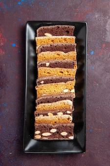 Bovenaanzicht heerlijke gesneden cake met noten in taartvorm op donkere achtergrond, zoete cacaocake, biscuittaart, suikerkoekjes