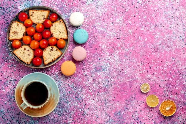Bovenaanzicht heerlijke gesneden cake met zure verse pruimen macarons en kopje thee op het roze oppervlak