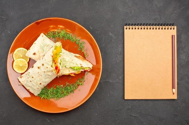 Bovenaanzicht heerlijke gesneden shaurma salade sandwich binnen plaat op de donkere achtergrond hamburger maaltijd sandwich brood snack